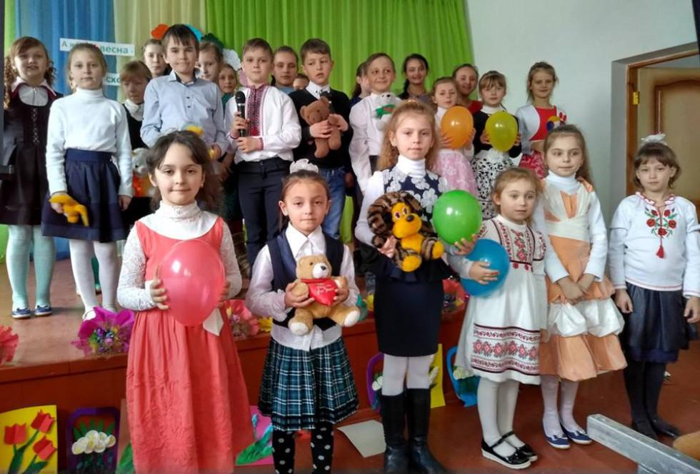 Діти тримають у руках кульки та іграшки